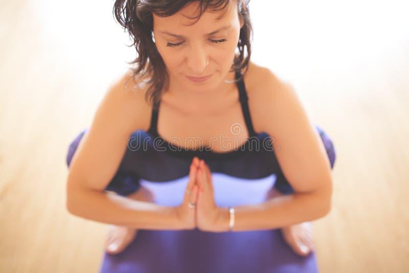 Mulher que faz a ioga no assoalho de madeira imagens de stock