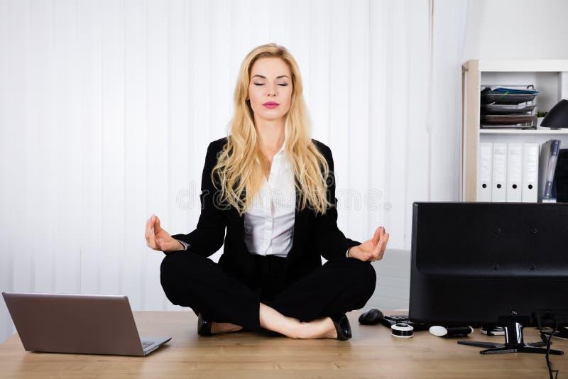 Mulher que faz a ioga no escritório fotos de stock royalty free