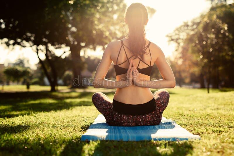 Mulher que faz a ioga no parque, posição reversa da oração Mulher da aptidão que faz a ioga de Pashchima Namaskarasana que senta- fotografia de stock