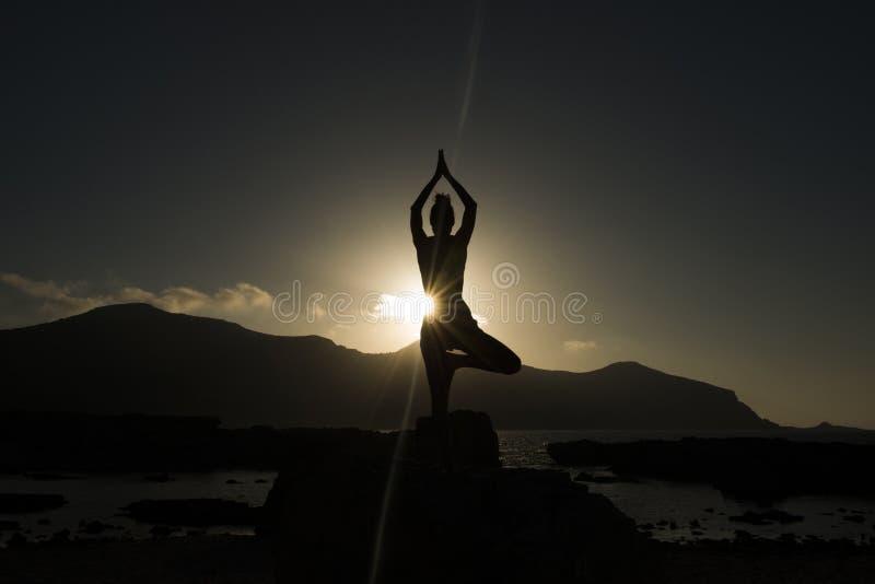 Mulher que faz a ioga no por do sol imagens de stock