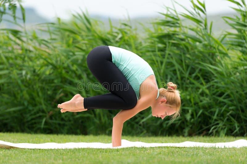Mulher que faz ioga o corvo levantar imagens de stock