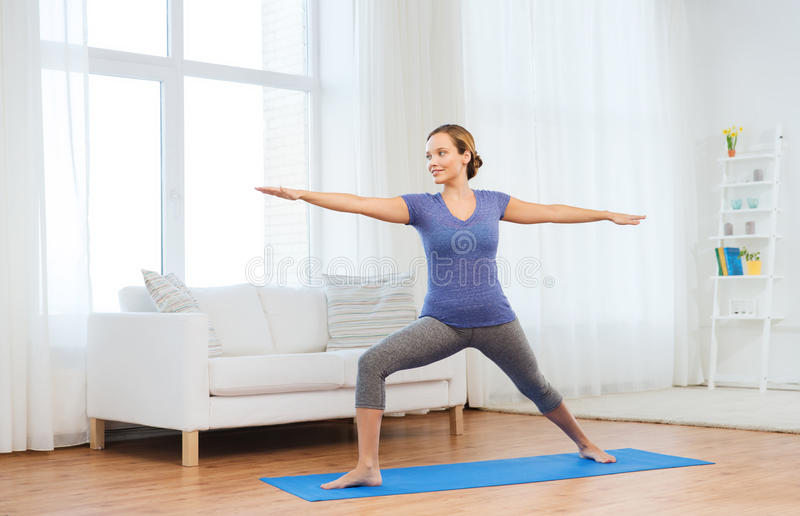 Mulher que faz ioga o guerreiro levantar na esteira foto de stock royalty free