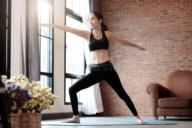 Mulher que faz ioga o guerreiro levantar na esteira em sua sala imagem de stock