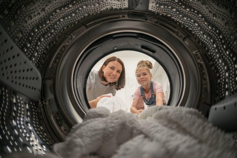 Mulher que faz a lavanderia com sua filha que alcança a toalha dentro da máquina de lavar fotos de stock