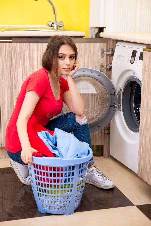 A mulher que faz a lavanderia em casa imagem de stock