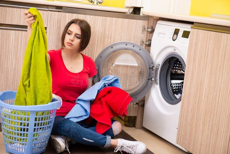 A mulher que faz a lavanderia em casa foto de stock royalty free