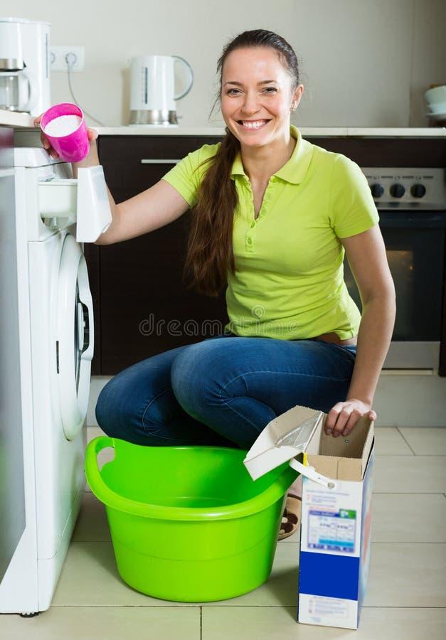 Mulher que faz a lavanderia em casa foto de stock