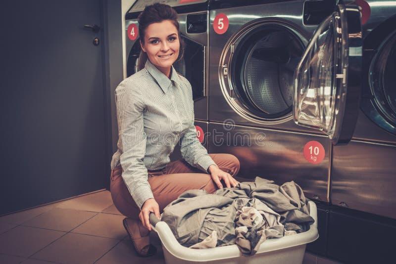 Mulher que faz a lavanderia na loja da lavagem automática imagens de stock royalty free