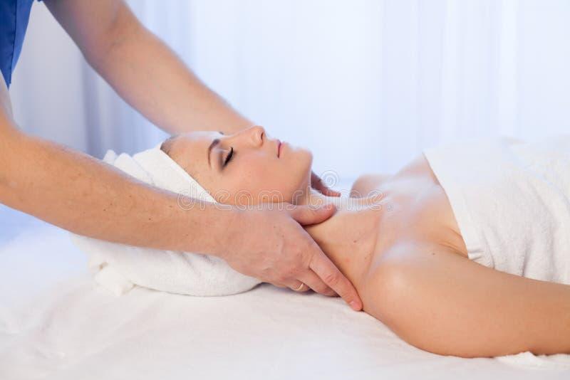 Mulher que faz a massagem médica da cara e do pescoço nos termas imagens de stock