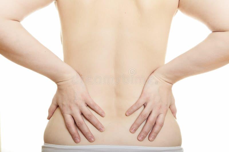 Mulher que faz massagens a parte traseira da dor fotografia de stock royalty free