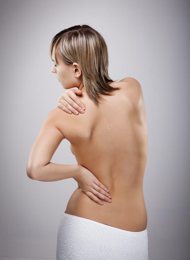 Mulher que faz massagens a parte traseira da dor fotos de stock royalty free
