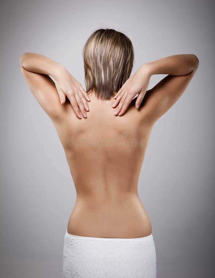 Mulher que faz massagens a parte traseira da dor imagem de stock royalty free