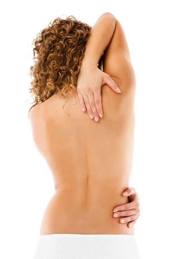 Mulher que faz massagens a parte traseira da dor imagens de stock