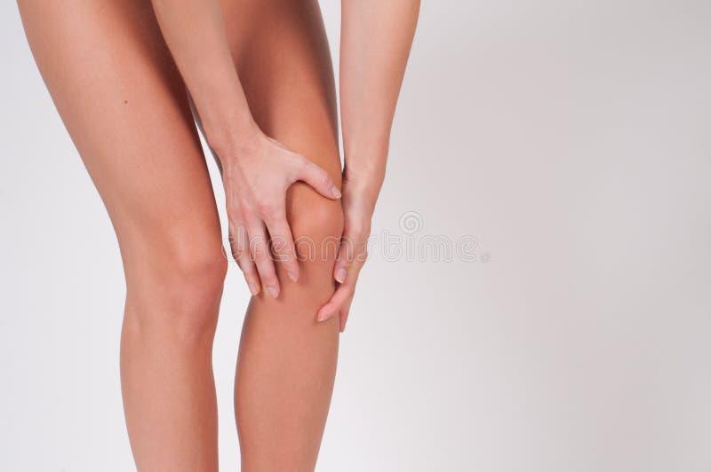 Mulher que faz massagens seu joelho doloroso, dor de sentimento no joelho foto de stock
