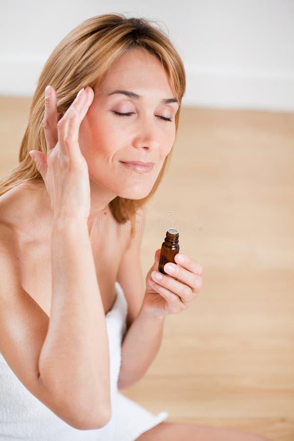 Mulher que faz massagens seus templos imagens de stock