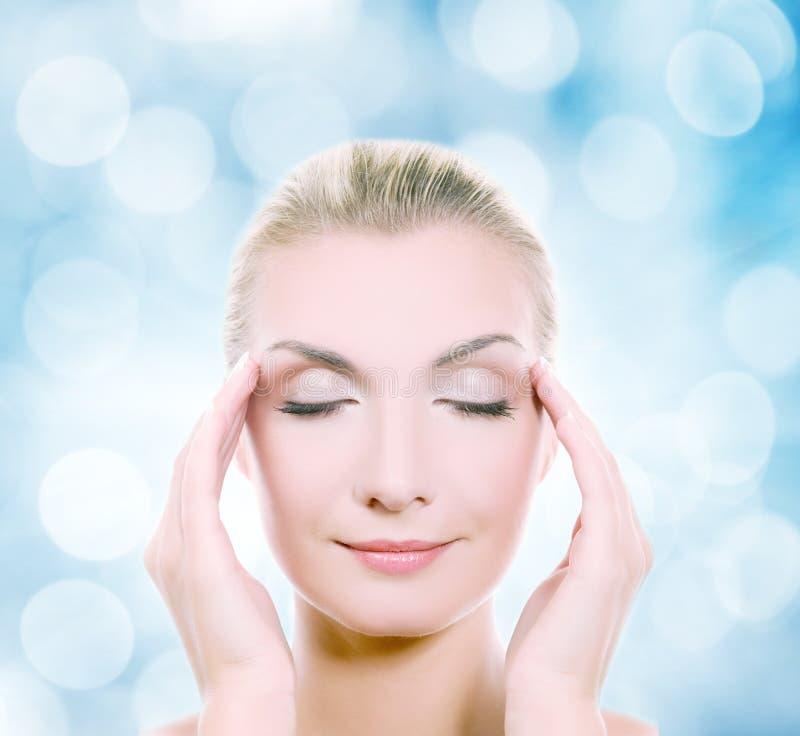 Mulher que faz massagens sua cabeça fotografia de stock