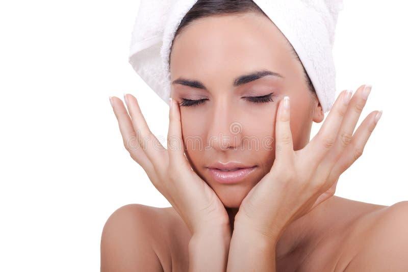 Mulher que faz massagens sua face fotografia de stock