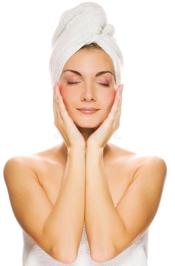 Mulher que faz massagens sua face foto de stock