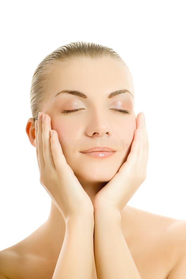 Mulher que faz massagens sua face imagens de stock royalty free