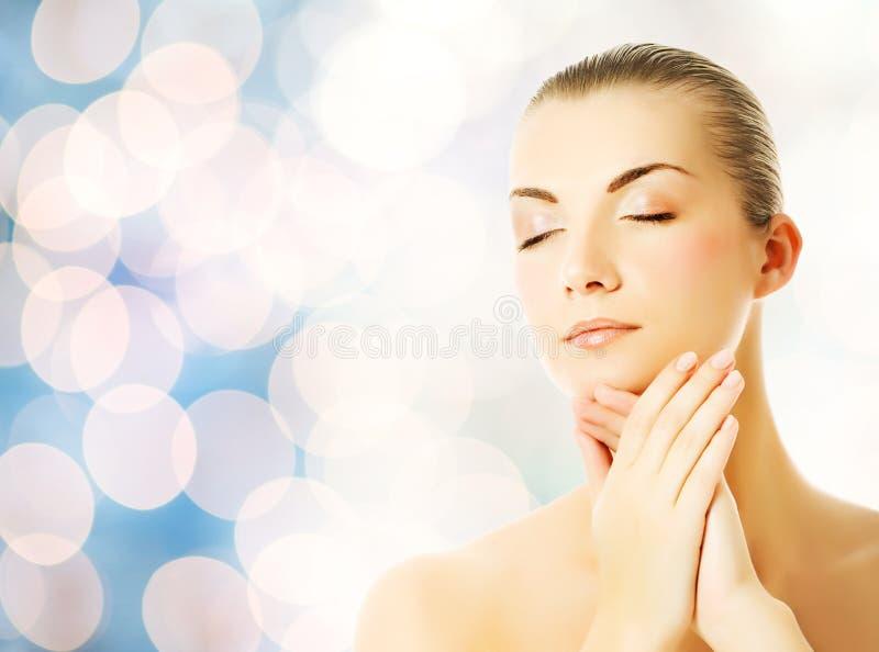 mulher que faz massagens sua face fotos de stock royalty free