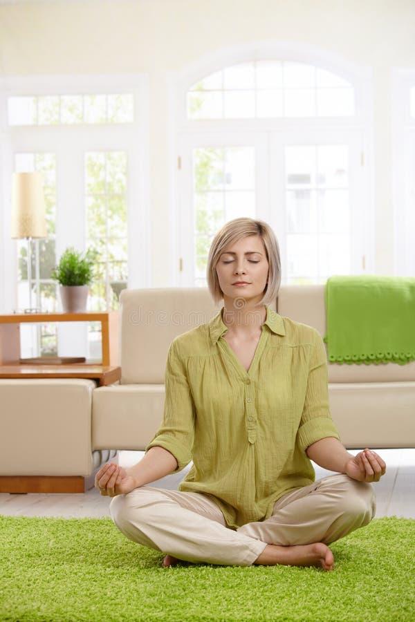 Mulher que faz a meditação da ioga em casa foto de stock royalty free