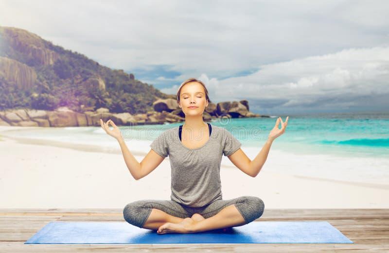 Mulher que faz a meditação da ioga na pose dos lótus na praia imagem de stock royalty free
