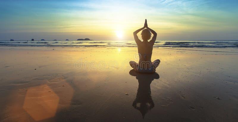 Mulher que faz a meditação perto da praia do oceano fotografia de stock royalty free