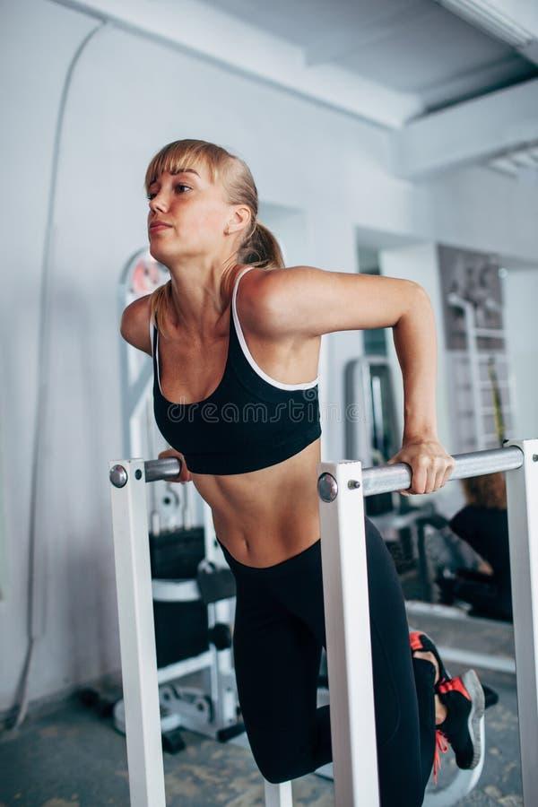 Mulher que faz mergulhos no gym fotos de stock royalty free