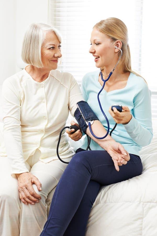 Mulher que faz a monitoração da pressão sanguínea fotos de stock