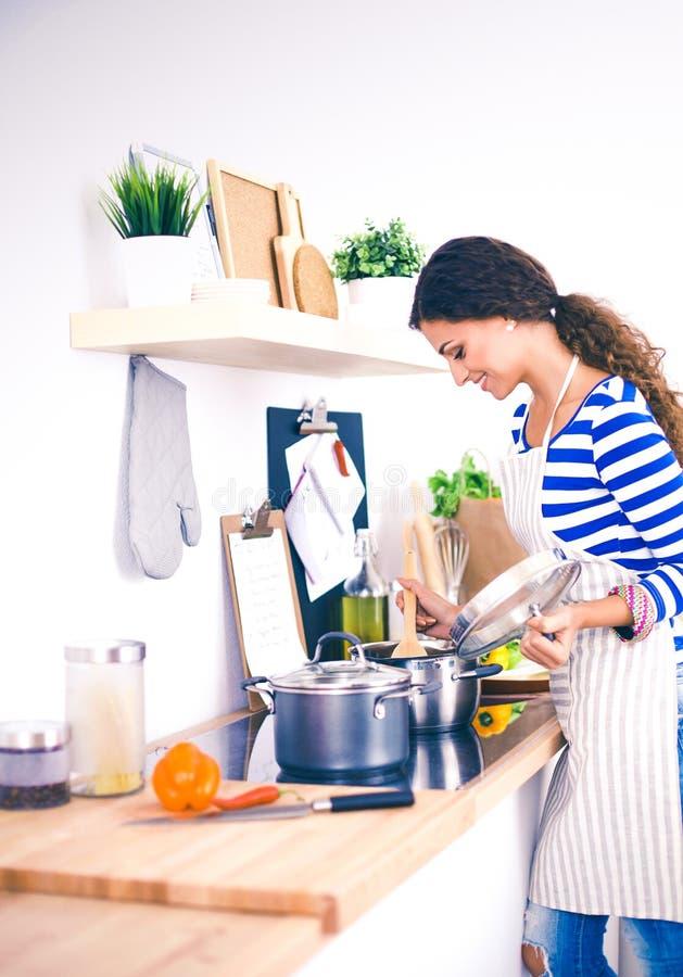 Mulher que faz o alimento saudável que está de sorriso na cozinha fotografia de stock