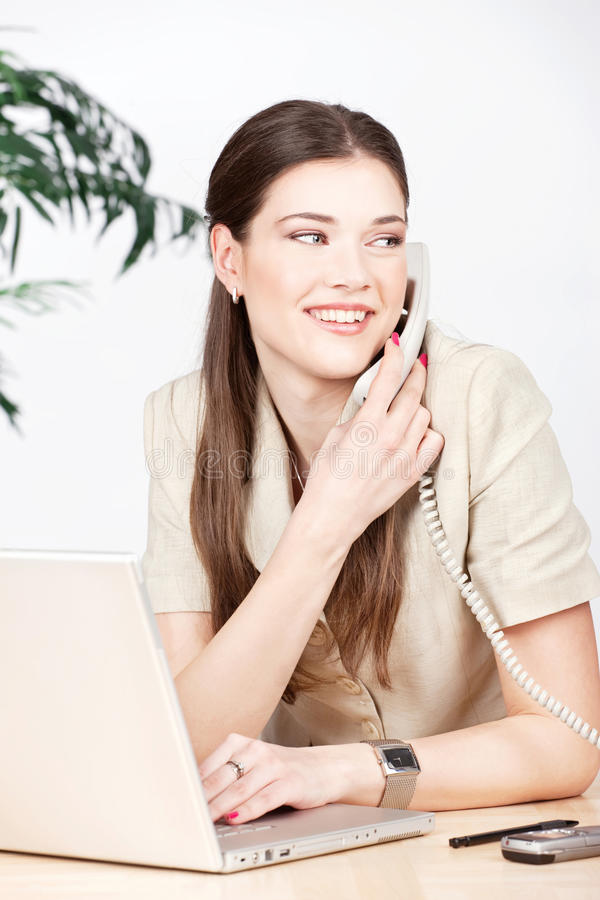 Mulher que faz o atendimento de telefone no escritório foto de stock