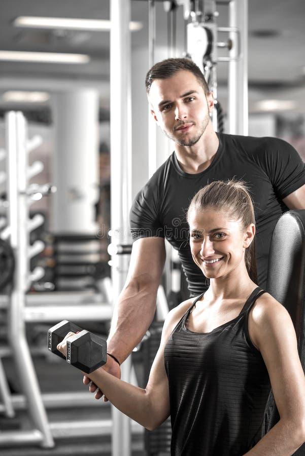 A mulher que faz o bíceps ondula no gym com seu instrutor pessoal imagens de stock royalty free