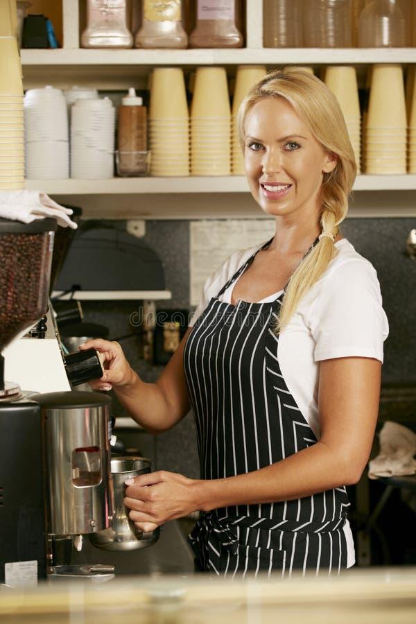 Mulher que faz o café na loja fotos de stock