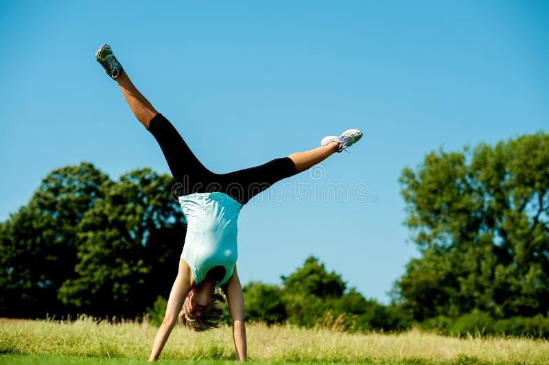 Mulher que faz o cartwheel em um campo imagem de stock royalty free