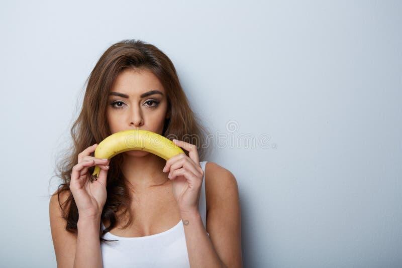 Mulher que faz o divertimento com uma banana imagens de stock royalty free