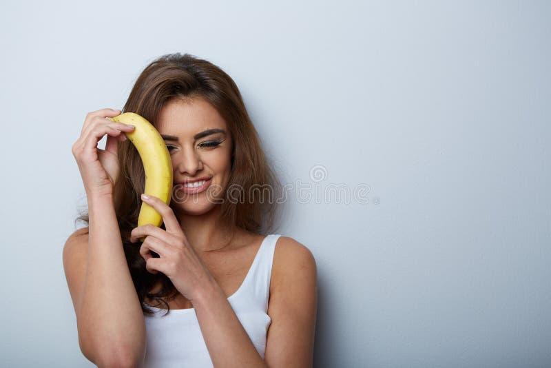 Mulher que faz o divertimento com uma banana imagem de stock royalty free