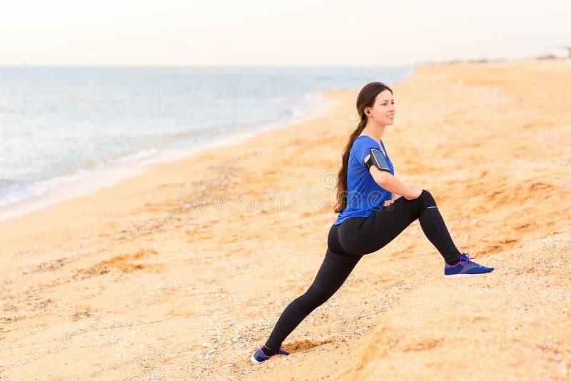 A mulher que faz o estiramento exercita na praia do mar imagem de stock royalty free