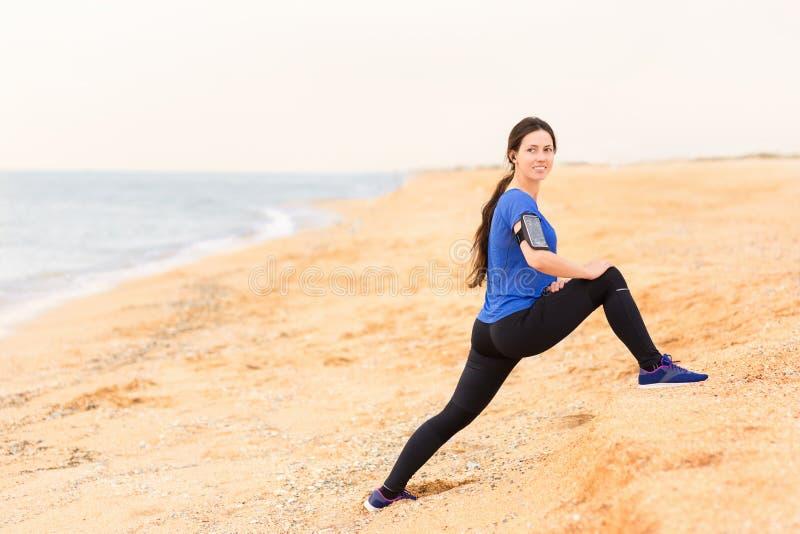 A mulher que faz o estiramento exercita na praia do mar fotos de stock royalty free