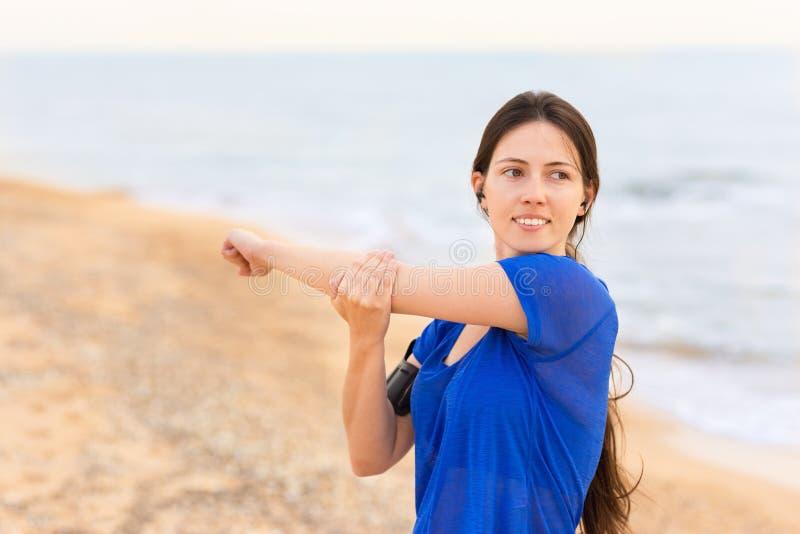 A mulher que faz o estiramento exercita na praia do mar foto de stock