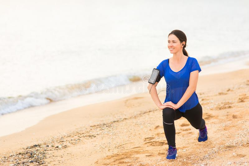 A mulher que faz o estiramento exercita na praia do mar fotos de stock