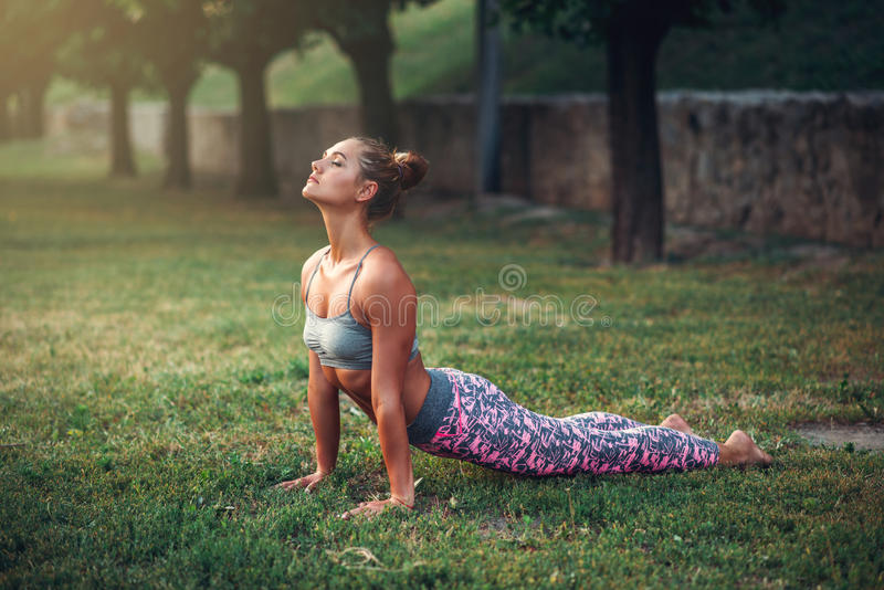 Mulher que faz o exercício da ioga no parque do verão fotos de stock royalty free