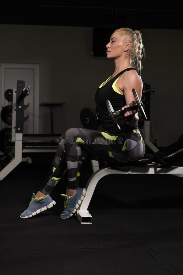 Mulher que faz o exercício do bíceps no Gym foto de stock