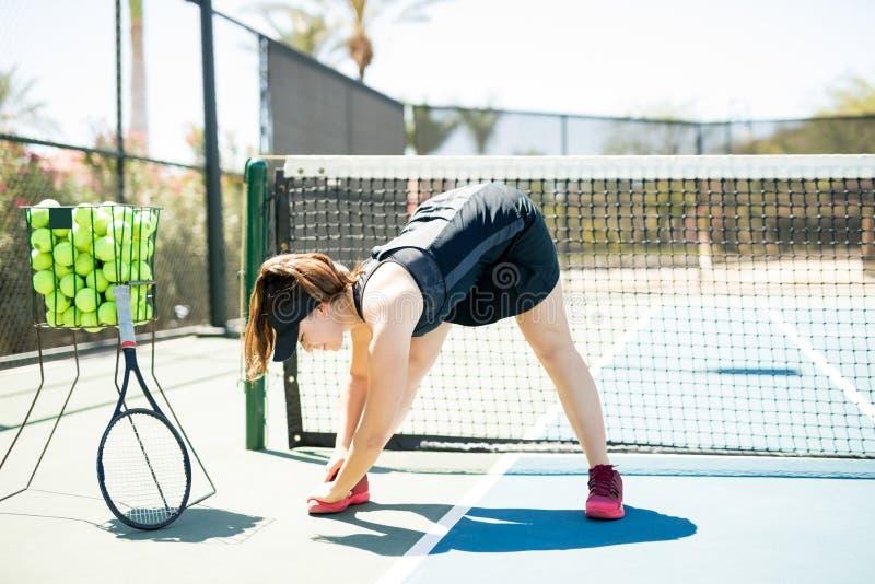 Mulher que faz o exercício do warmup no campo de tênis fotografia de stock