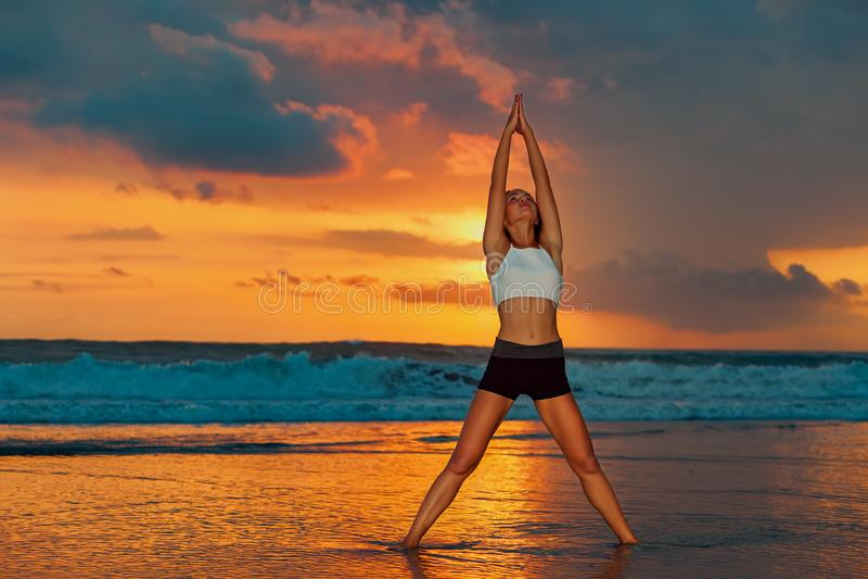 Mulher que faz o exercício na praia do por do sol fotos de stock
