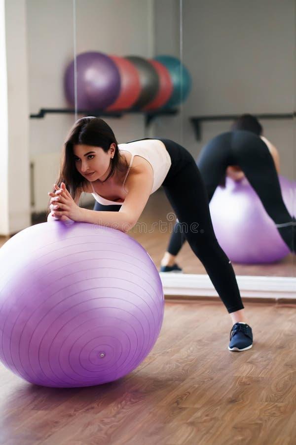 Mulher que faz o exercício usando a bola ostentando no gym foto de stock