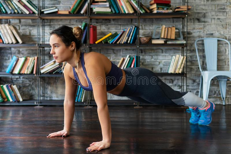 A mulher que faz o impulso levanta o exercício durante o treinamento da aptidão no assoalho em casa imagem de stock