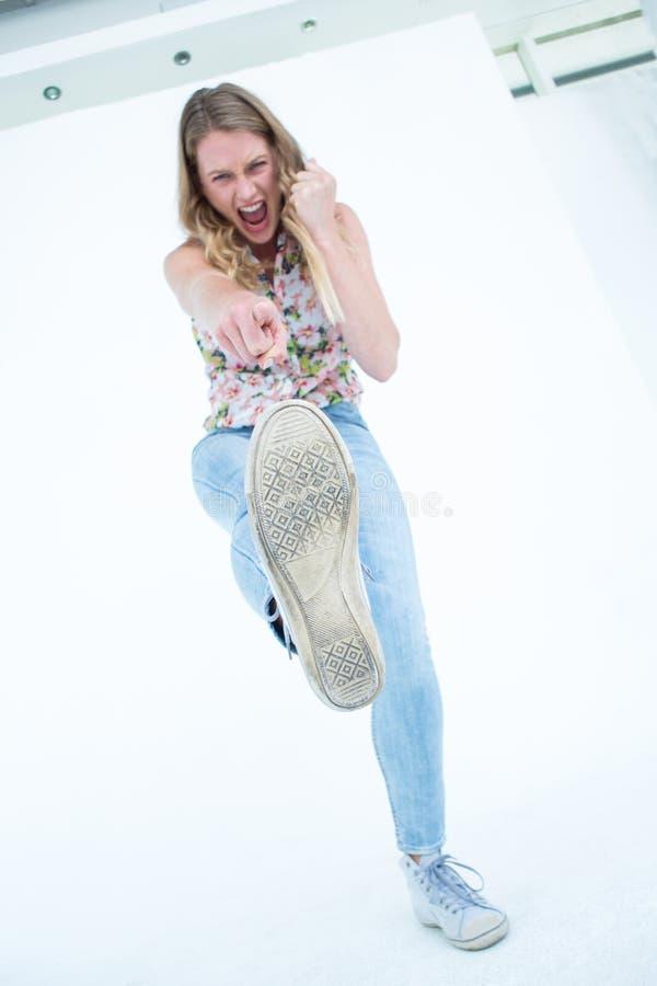 Mulher que faz o pontapé do karaté fotografia de stock