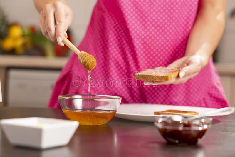 Mulher que faz o sanduíche do mel e da manteiga imagens de stock royalty free