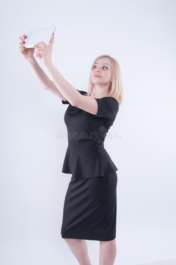 A mulher que faz o selfie com a tabuleta no branco isolou o fundo Feche acima da menina bonita loura nova no vestido preto imagem de stock royalty free