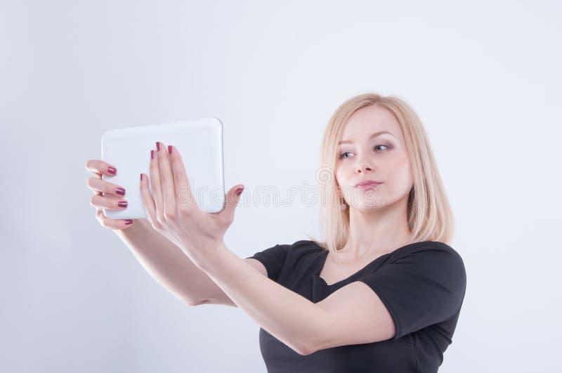 A mulher que faz o selfie com a tabuleta no branco isolou o fundo Feche acima da menina bonita loura nova no vestido preto imagens de stock